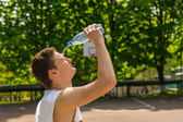 Athletic Man Pouring Water from Bottle onto Face — Stock Photo