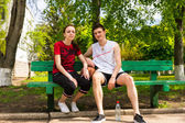Young Couple Sitting on Park Bench with Basketball — Stock Photo