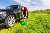Woman with Bucket Wringing Out Sponge Next to Car — Stock Photo