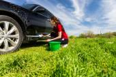 Woman Washing Black Car in Field with Soapy Sponge — Stock Photo