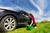 Woman with Bucket Washing Black Car in Field — Stockfoto