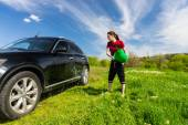 Woman Washing Car with Bucket of Water in Field — Stock Photo