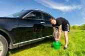 Man Washing Car Using Sponge and Bucket in Field — Stock Photo