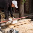 Man Using Power Saw to Cut Planks of Wood — Stock Photo #74803093