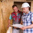 Construction Workers Consulting Plans in New Home — Stockfoto #74802203