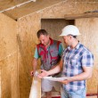 Foreman with Plans Monitoring Worker In New Home — Stockfoto #74802219