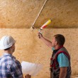 Foreman Watching Worker Apply Caulking in New Home — Stockfoto #74802355