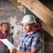 Foreman with Plans Monitoring Work on Staircase — Stockfoto #74802685