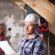 Foreman with Plans Monitoring Work on Staircase — Stockfoto #74802739