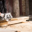 Man Using Power Saw to Cut Planks of Wood — Stock Photo #74802965