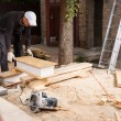 Man Using Power Saw to Cut Planks of Wood — Stock Photo #74802975