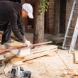 Man Using Power Saw to Cut Planks of Wood — Stock Photo #74803009