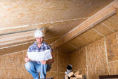 Builder Reading Plans Inside Unfinished Home — Stock Photo
