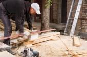 Man met behulp van kracht zag te snijden planken van hout — Stockfoto