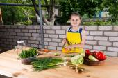 Young girl chopping vegetables for bottling — Stock Photo