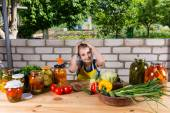 Girl at Table Covered by Vegetables and Preserves — Stock Photo