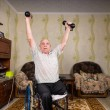 Постер, плакат: Invalid old man puts his hands up with dumbbells