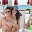 Young Couple on Lounge Chair at Beach Resort — Stock Photo #81696908