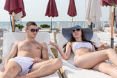 Young Couple Talking While Resting on Loungers — Stock Photo
