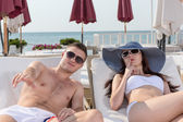 Sexy Young Couple Resting on Lounge Chairs — Stock Photo