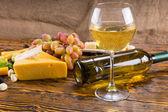 チーズとブドウの木のテーブルの上に白ワイン — ストック写真