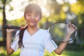 Little asian girl holding a badminton racket — Stock Photo
