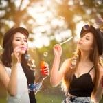 Beautiful asian teen girls blowing soap bubbles — Stock Photo #57137343