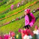 Smiling asian little girl sitting on flower field — Stock Photo #63651235