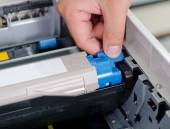 Male hand putting and lock color printer toner — Stock Photo