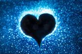 Heart silohuette on a blue bokeh background — Stock Photo