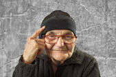 Elderly woman has an idea, pointing with finger on her head. — Stock Photo