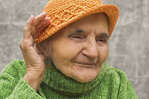 Elderly woman holding hand close to an ear. — Stock Photo