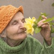 Elderly woman smelling yellow rose flower — Stock Photo #55052557