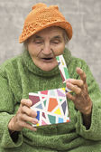 Happy and surprised elderly woman after opening gift box. — Stock Photo