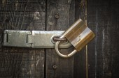 Padlock and old metal hasp on an old wooden door — Стоковое фото