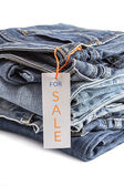 Pile of blue jeans with tag label. — Stock Photo