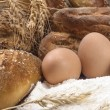Still life with raw eggs and fresh crunchy bread. — Stock Photo #67099151