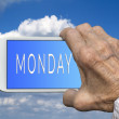 Smart phone in old hand with days of the week - M onday on scree — Stock Photo #78453854