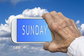 Smart phone in old hand with days of the week - Sunday on screen — Stock Photo