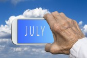Smart phone in old hand with month of the year - July on screen. — Stock Photo