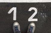 1 と 2 の番号を持つアスファルト道路上のスニーカー — ストック写真