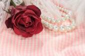 Closeup red rose with pearl necklace on pink fabric background. — Stock Photo