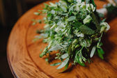 Green bouquet in a rustic style on a wooden table — Stockfoto