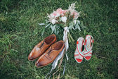 Bouquet of pink and white peonies and greens lying on the grass with boots made of brown leather groom and bride's shoes — Stock Photo