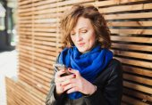 Smiling young woman using mobile smartphone on the street — Stock Photo