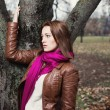 Pensive young  brunette girl standing near tree in autumn park — Zdjęcie stockowe #58785867