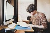 Jeune homme à la maison en utilisant un ordinateur, développeur indépendant ou un desig — Photo