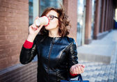 Young stylish woman drinking coffee to go in a city street  — Stock Photo