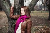 Pensive young  brunette girl standing near tree in autumn park — 图库照片