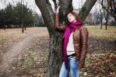 Pensive young  brunette girl standing near tree in autumn park — Stockfoto